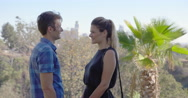Couple talking in park with Los Angeles skyline in background 4K Stock Footage