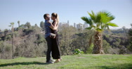 Couple hug in park with Los Angeles skyline in background 4K Stock Footage