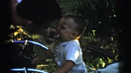 1961: little boy biting and playing with arm and hand of a man and a small ball Stock Footage