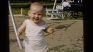 1961: a baby walking in the playground DETROIT, MICHIGAN Stock Footage
