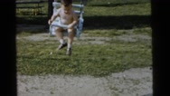 1961: a young boy swinging rapidly on a traditional swing set in the yard Stock Footage