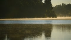Fog rises up on a lake in early morning Stock Footage