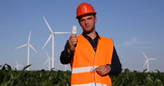 Electricity Engineer Comparing Show Light Bulb Looking Camera Wind Turbine Field Stock Footage