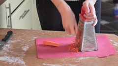 Woman grating carrot on grater and making soup Stock Footage