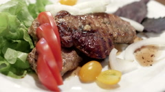Pork steak with cherry tomatoes and herbs on a white plate Stock Footage