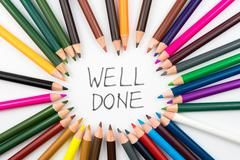 Colouring pencils in circle arrangement with message WELL DONE Stock Photos