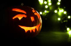Carved face of pumpkin glowing on Halloween on green bokeh light background Stock Photos