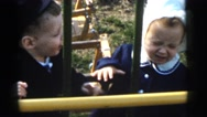 1961: two toddlers playing by a swing set on a beautiful afternoon DETROIT Stock Footage