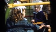 1961: bossy sister pushes siblings around on swings DETROIT, MICHIGAN Stock Footage