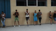 Young men and women stand on central street in Havana near a wall of the Stock Footage