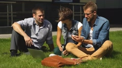 Three students sitting on lawn Stock Footage