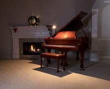 Piano with reading light and glowing fireplace during holiday season Stock Photos