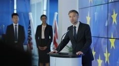 4K Politician making a speech at press conference, EU flag in background Stock Footage