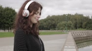 Pretty woman portrait smiling wearing headphones outdoors Stock Footage