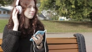 A young woman listens to her music in the park. Stock Footage