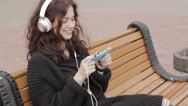 Young adult woman in headphones using mobile phone outdoors Stock Footage