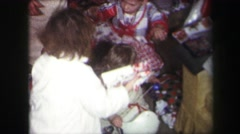 1974: group of children opening presents on christmas morning in the living room Stock Footage