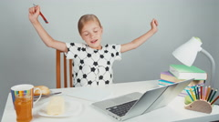 Schoolgirl 7-8 years making sandwich with butter sitting at the desk Stock Footage