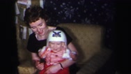 1974: woman holds a toddler in a homemade color video around the christmas Stock Footage