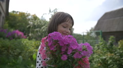 Little Girl gets pleasure from flowers Stock Footage