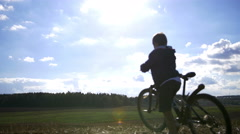 Boy with a bicycle goes over the mountain Stock Footage
