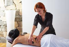 Hot stone massage in woman back physiotherapist Kuvituskuvat