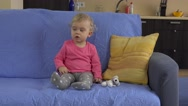 Lovely baby get tv remote control and concentrate on watching television Stock Footage