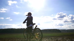 Boy with a bicycle on the mountain looks and goes Stock Footage