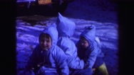 1974: three kids wearing winter clothing are playing on a sled  Stock Footage