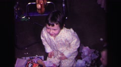 1974: children are opening gifts at christmas in their pajamas by the christmas Stock Footage