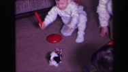 1974: toddler catches bouncing puppy toy as mom watches on LYNBROOK, NEW YORK Stock Footage