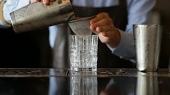 The bartender pours a glass of the finished cocktail Stock Footage