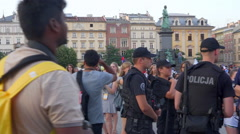 Police officers group on crowded square with teenagers dancing - Krakow WYD 2016 Stock Footage