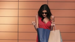 Attractive brunette opens her shopping bags and enjoys the purchases Arkistovideo