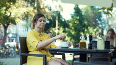 Woman mixing beverage in the cup while relaxing in the outdoor cafe Stock Footage