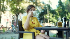 Woman drinking coffee in the outdoor cafe and answers cellphone Stock Footage