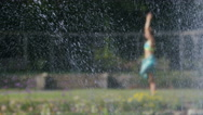 Focus on water fountain as woman does yoga in blurred background, in slow motion Stock Footage