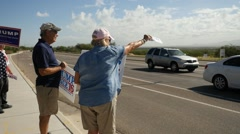 Trump supporters waving signs at an intersection Stock Footage