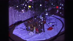 1974: a christmas tree is seen with a child opening presents LYNBROOK, NEW YORK Stock Footage