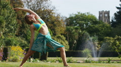 Attractive woman relaxing with yoga in the park, in slow motion Stock Footage