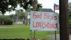 Sign Stating 'God Bless Lousiana' in Foreground of US Flag Stock Footage