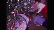 1974: kids playing with a toy train under the christmas tree LYNBROOK, NEW YORK Stock Footage
