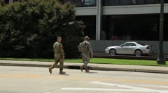 Uniformed soldiers walking across street to building Stock Footage