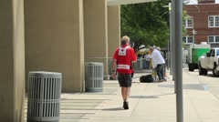 Red Cross Worker With Vest Walking in Town Stock Footage