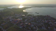 Flying over the houses near the lake at sunset Stock Footage