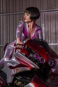 Brunette woman mounted on a modern motorcycle customized and original, it car Stock Photos