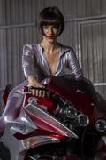Fashion brunette woman mounted on a modern motorcycle customized and original Stock Photos