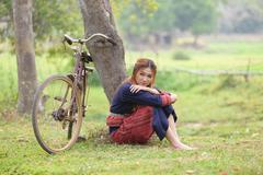 Young asian women inattentive sitting next to tree with bike in rice field. Stock Photos
