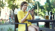 Woman drinking coffee while texting on smartphone in the outdoor cafe Stock Footage
