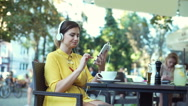 Absorbed woman listening music and browsing internet on tablet Stock Footage